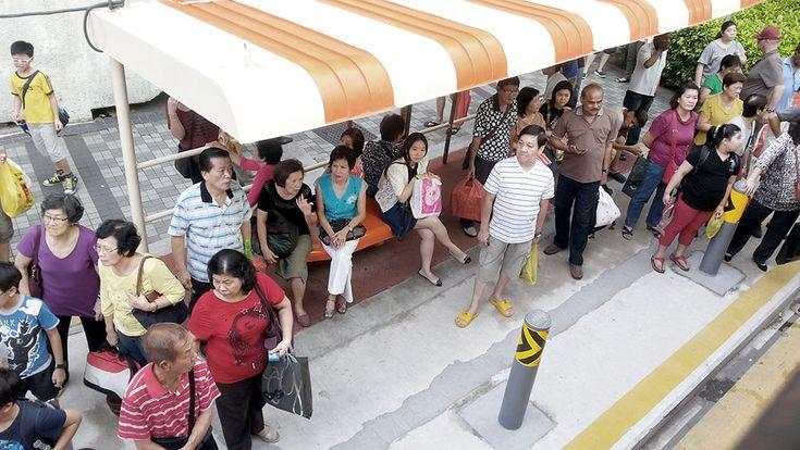 Menschen warten ohne Handy an einer Bushaltestelle