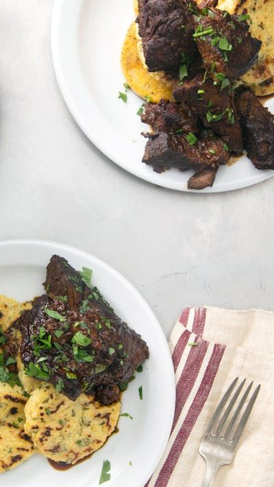 As the weather cools outside, warm up with hearty braised beef dripping in sauce with warm polenta cakes.