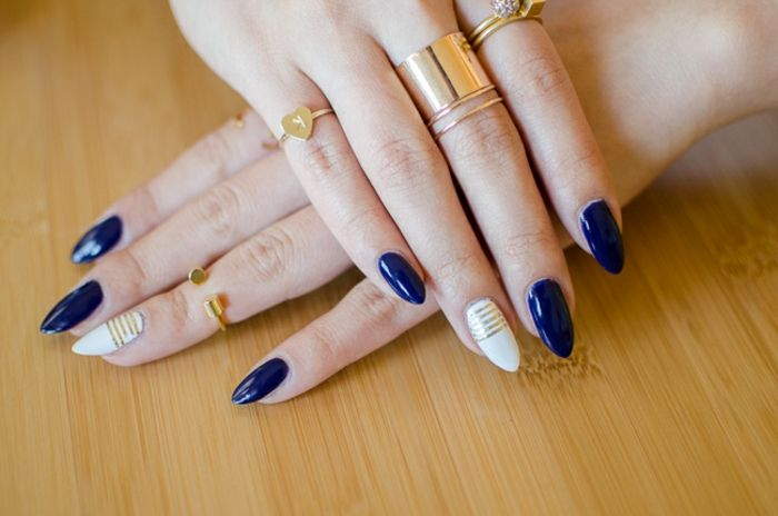 navy blue and white nail polish, on long oval nails, decorated with several thin, golden colored stripes, hands with several different golden rings
