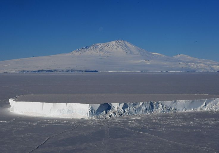 An iceberg lies in the Ross Sea with Mount Erebus in the background near McMurdo Station in Antarctica, November 11, 2016. A sheet of meltwater lasted for as long as 15 days in some places on the surface of the Ross Ice Shelf, the largest floating ice platform on Earth, during the Antarctic summer of 2016. (Agence France-Presse via Getty Images)   Scientists stunned by Antarctic rainfall and a melt area bigger than Texas