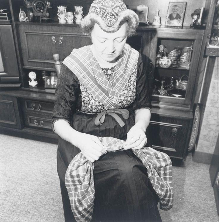 Demonstratie van het vouwen van kleding in Staphorst-Rouveen door Mevrouw J. Timmerman-Slager uit Rouveen, t.b.v. het onderzoek voor de tentoonstelling 'Kleding met een vouwtje' in het Nederlands Openluchtmuseum. Mevrouw Timmerman demonstreert het vouwen van de rode schouderdoek.