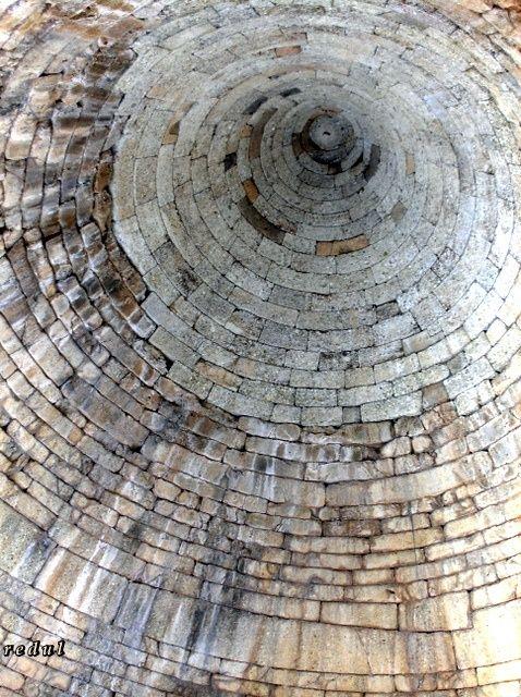 ** Interior del TESORO de ATREO, Micenas -  La cúpula de hileras en forma de anillos superpuestos cierran el espacio en una falsa bóveda, descarga en los muros la carga del conjunto sin necesidad de soporte central, se consigue espacio diáfano, el más grande hasta la construcción del Pantheon en Roma 1.000 años más tarde