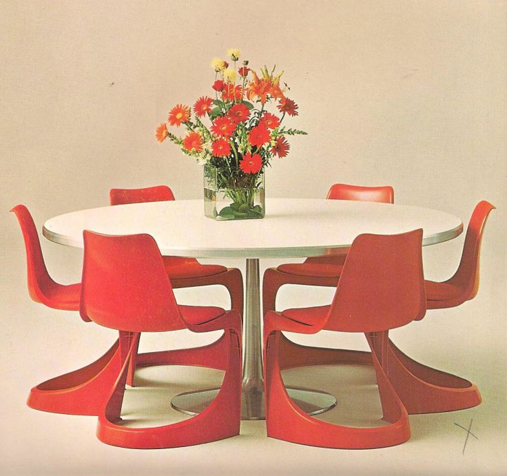 A modern round dining table in white with red flowers and 6 red Steen Ostergaard designed chairs around it