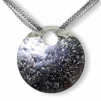 Handmade in our Mayfair workshop, the stunning contemporary silver necklace definitely makes a statement. With a unique texture that glistens.  Each disc is hammered to create a textured effect and is then polished to finish.  The disc is suspended on six layers of silver chain which culminates in a luxurious and glamorous style.  Disc Size 55mm