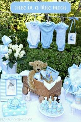 """Add pretty details like moons and stars to the traditional blue theme for a bit of spice. The book """"The Magic Blanket"""" is tucked in an adorable wooden wagon complete with a teddy bear!"""