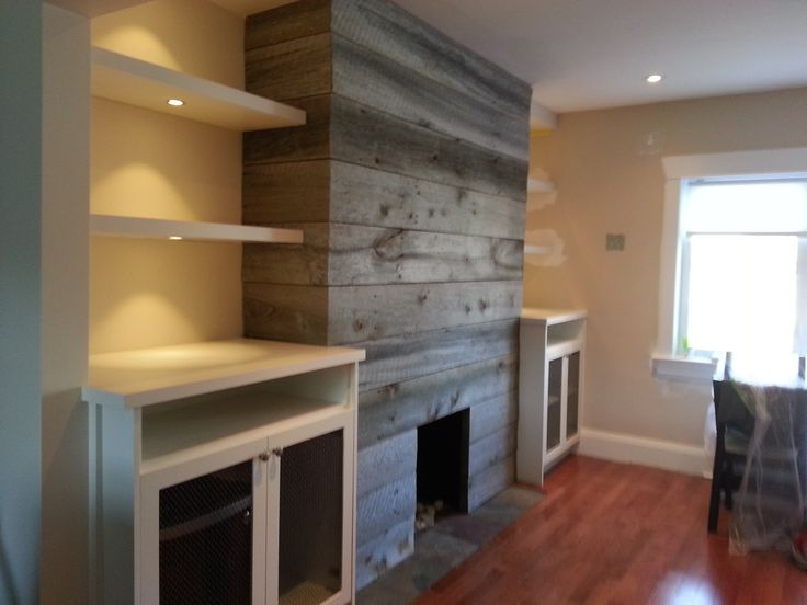 Fireplace clad in barn board with white cabis and floating shelves Cabiry Pinterest