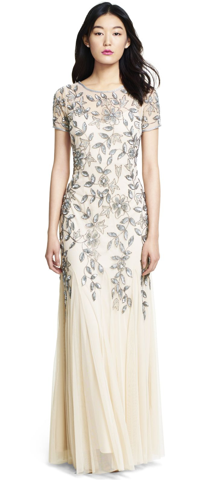 This truly glamorous gown features a delicately beaded floral pattern that cascades elegantly down the dress.