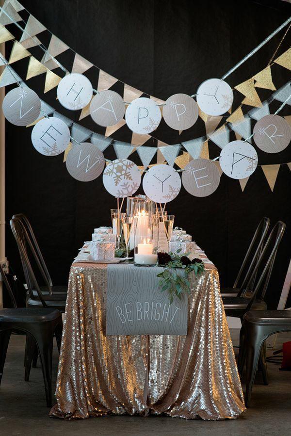 feierliche tischdeko für silvester. funklend eingedeckter Tisch und Girlanden und Wimpelketten aus metallischen Papieren.