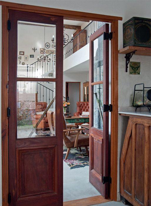 Todas las aberturas de la casa son de madera de cedro recuperadas (De ayer y de siempre), y se codean con algunas de hierro y vidrio repartido hechas a nuevo o recuperadas. Aquí, una puerta doble de madera que comunica el living con la cocina y anticipa algo de su estética.