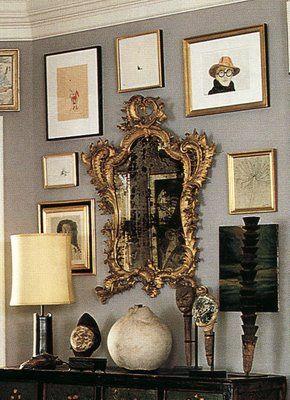 Antique mirror with mix of art on gray wall anchored by black bureau and lamp--Foyer of Kate Spade