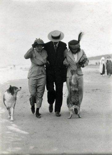 Strandleven. Strandwandelingen. Man met twee dames en twee honden lopen tegen de wind,  aan het strand.  Plaats en land onbekend, foto Badnummer 1913.