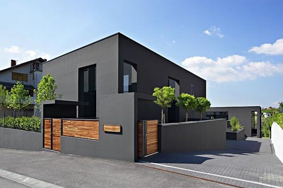 this is the crux of it - black house (with dark grey accents) and wood tone awning over patio, slats by deck and facing on garage doors