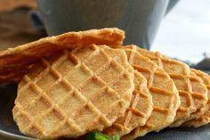 Dunne, harde wafeltjes of lukken koekjes: net gebakken in een wafelijzer, naast een kopje koffie