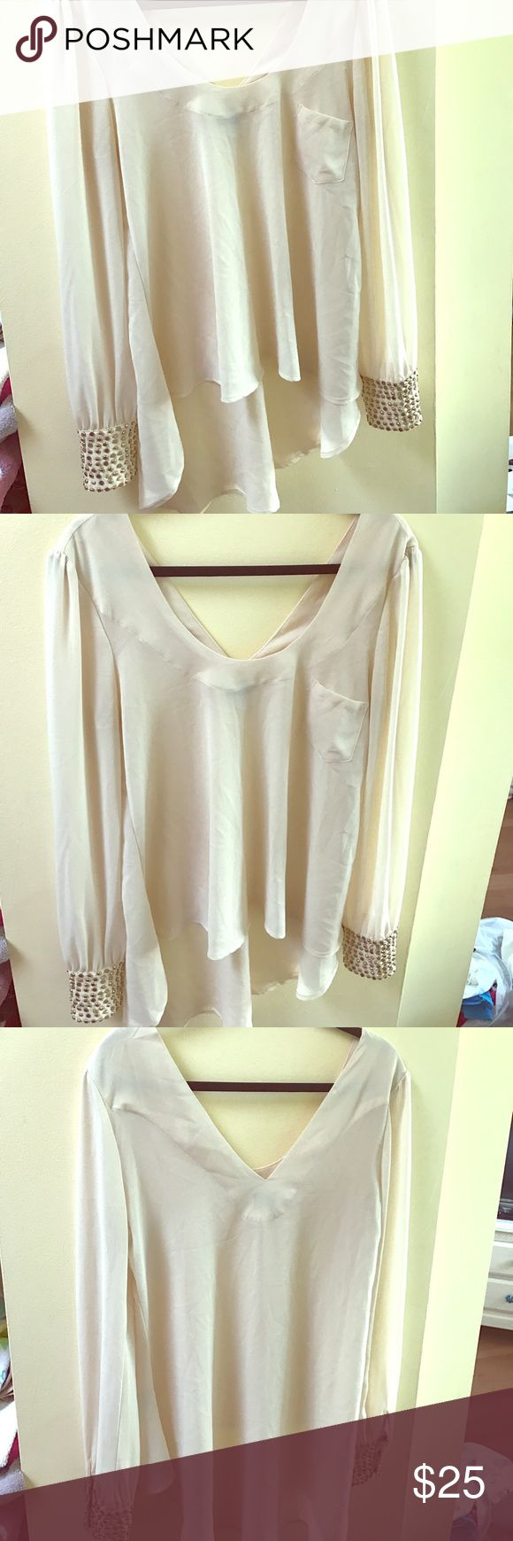 Beige long sleeve top with beaded wrists Loose & light beige colored long sleeved top with gold & brass beads around the wrist. Length is longer in the back. Very trendy. Perfect condition. Very J Tops Tunics