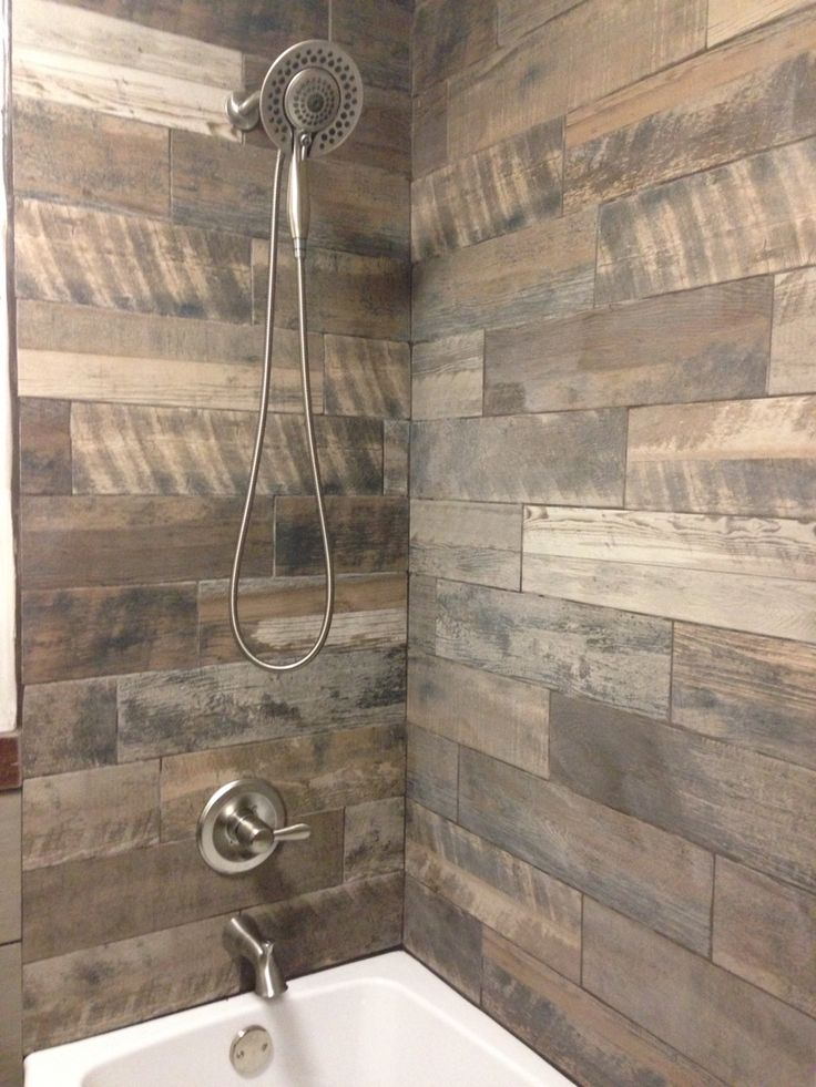 Very rustic shower with the wood looking porcelain tiles on the ...