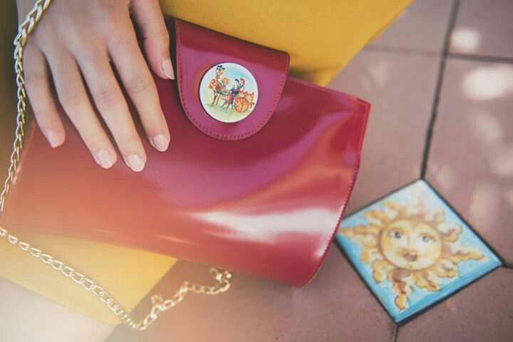 #Pochette rossa in pelle con #carrettosiciliano #dipintoamano su tondo di #ceramica di 4 cm posto al centro della ribaltina. Rivestimento interno in pelle. Tracolla: catena dorata. Lunghezza: 22 cm Altezza: 16 cm. Compra ora! #borseartigianali #bags #Decortack #modadonna #MadeinSicily Contatti: info@decortack.it - 3294198247
