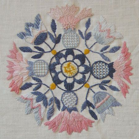 Blekingesom, Swedish embroidery -- features light pinks and dark blues [historically red was used before pink]. This piece incorporates schattersöm, a scalene satin stitch, the stem stitch and French knots.