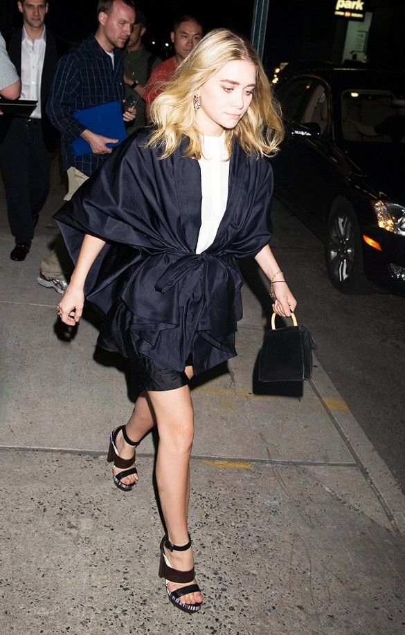 Ashley Olsen wears a white top, navy belted coat, and platform sandals