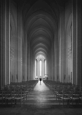Vesa Pihanurmi - Grundtvig's Church. A black and white photograph of a church with a high arch and rows of chairs.