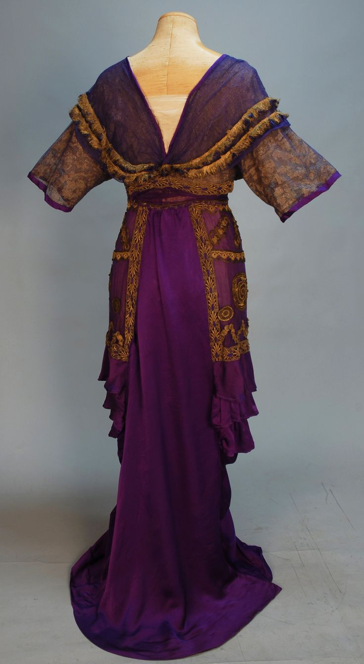 LUCILE SILK and METALLIC LACE BELLE EPOCH GOWN, Winter 1911. Trained royal purple charmeuse with short sleeve wrap bodice of gold metallic lace under purple net trimmed with gold fringe and silk flowers, draped hobble skirt with ruffled chiffon side panels heavily appliqued in metallic gold, open at front hem with tassel over chiffon insert, demi-train