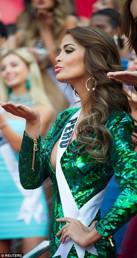 Blowing kisses to the adoring crowds, Peru's Miss Spoya dazzled in a sparkling green dress with a daringly low-cut neckline, pictured left, while last year's winnerColombia's Paulina Vega, right, wows in a floor-length gold sequin gown