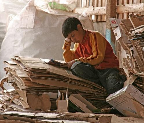 Chilean boy reading at the recycling cooperative where his parents work classifying garbage. Located in Puente Alto, Santiago de Chile