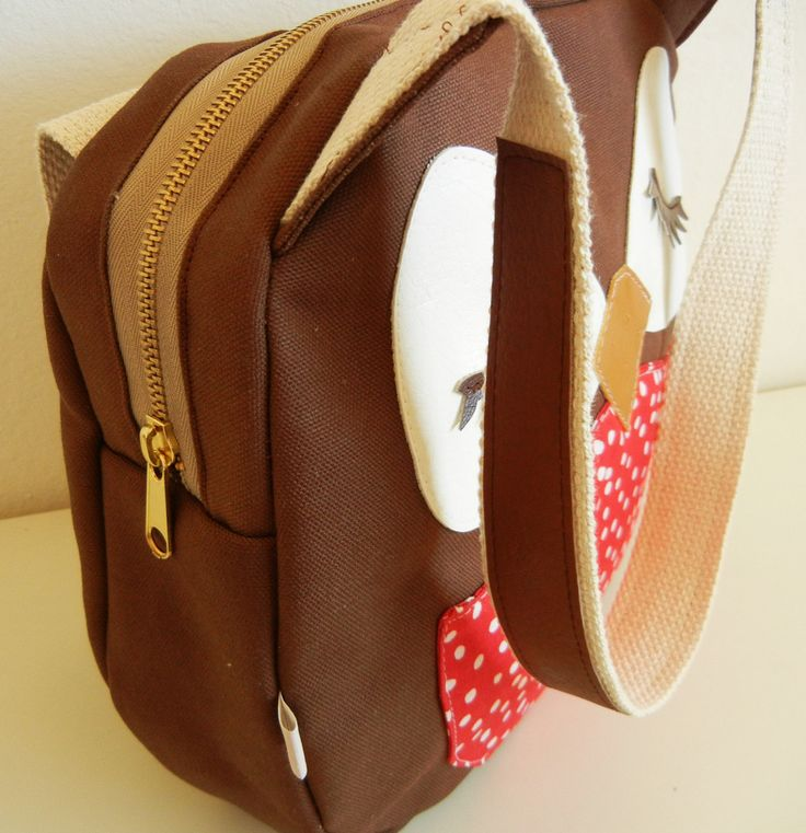 This is a canvas shoulder bag featuring Stewart the Owl!    The brown duck canvas shoulder bag features a tan/brass metal zipper, natural cotton webbing straps,,and a cuore flag label at the left corner of the body. All inner seams are taped/finished. The cotton webbing straps feature brown vinyl contrast detail at the top.    Stewart the Owls eyes are crafted from white vinyl, his lashes are brown vinyl, his beak is a peanut brittle vinyl, and his front pouch is cotton red polka dot print…
