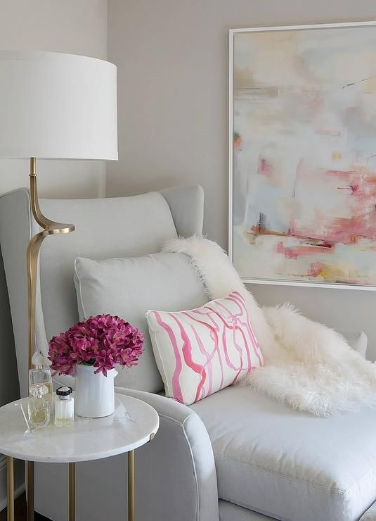 A dove gray velvet wingback chaise lounge topped with a pink brush strokes pillow and a sheepskin throw sits catty corner between a round brass and marble accent table lit by a curved brass floor lamp and a pink and gray abstract art piece hung on a light gray wall in this gorgeous transitional bedroom.
