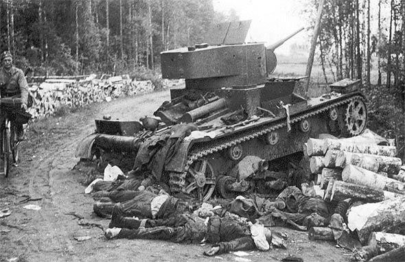 Osin tuhoutunut tankki, jonka vierellä miesten ruumiita. Pyöräilijä ajaa ohi.