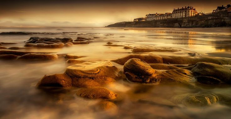 Recent storms have removed a lot of sand from the beach at Whitley Bay in the UK exposing these beautiful orange worn down rocks.