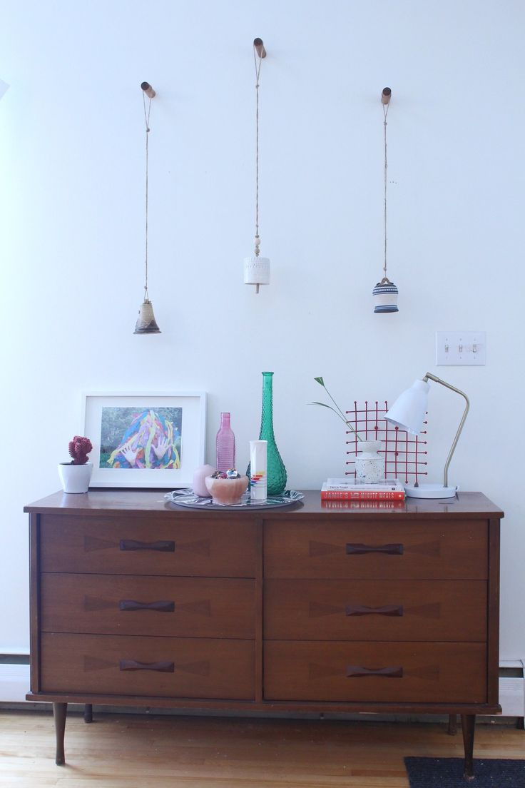 Bright, colourful eclectic midcentury credenza before and after makeover decor using ceramic bells and wooden dowel wall hooks
