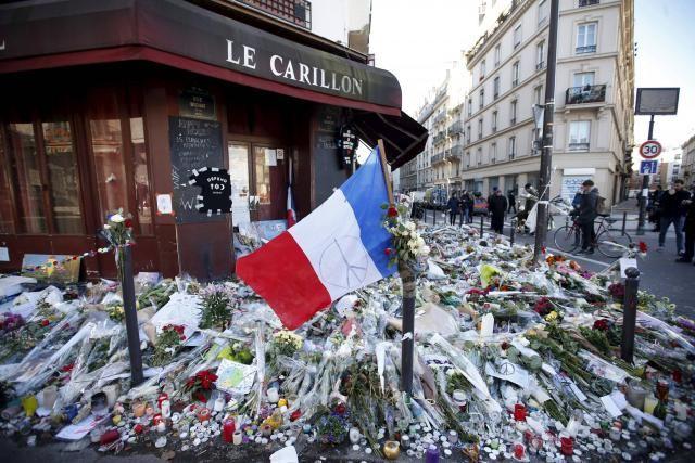 Le drapeau bleu-blanc-rouge trône au milieu des fleurs, des bougies et des messages devant le restaurant Le Carillon, à Paris.