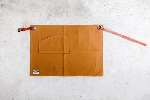 This waist apron is made from durable heavy-weight canvas. It has a lot of personality for a small apron with two frontpockets, inside phone pocket, hand-cut leather straps, brass hardware and hand-hammered brass rivets.