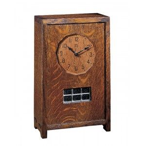 Small Mantel Clock A reissue of a Gustav Stickley 1912 original, this clock features a battery powered quartz movement. A small leaded glass window is located beneath the face. Available in solid oak.Dimensions:H13¾ W8½ D4¼
