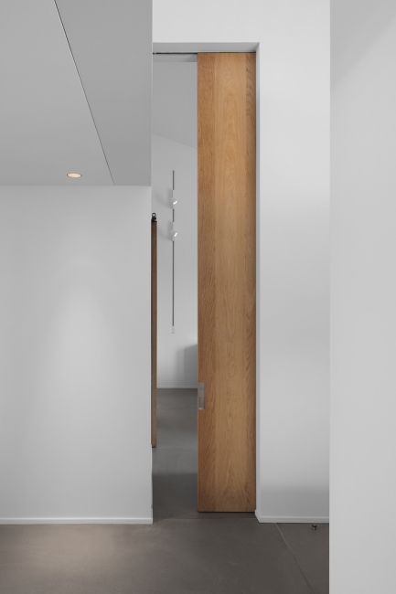 Tall wooden sliding door by Peter Ivens.