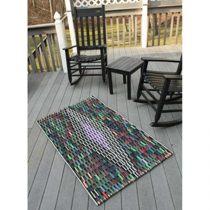Area rug made from scrap material reclaimed from flip flop factories.