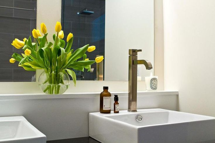 Modern bathroom features a black vanity lined with his and her vessel sinks and modern faucets placed under a built-in shelf topped with yellow tulips under his and her frameless mirrors.