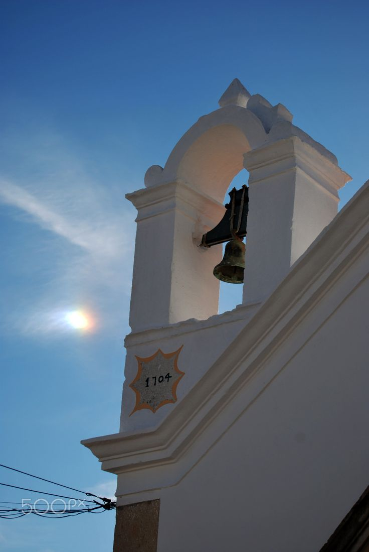 The Chapel - Bell tower of the Santo Cristo chapel in Moncarapacho, Olhão. The village saw an extensive growth in modern times which led to the creation of new religious spaces like this chapel. There is a possibility that this chapel was built on top of a pagan temple not only re-using sacred places by different generations but also by different religions.  However to prove this more investigation would be needed and Moncarapacho still have many secrets to be revealed.