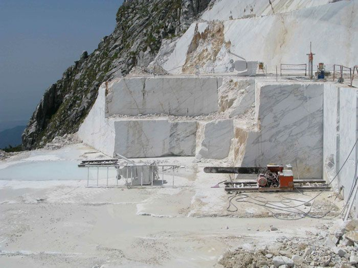 A large hydraulic chainsaw is used to undercut the marble before wire saws completely dislodge the block material. Henraux marble quarry, Apennine mountains, Carrara, Italy