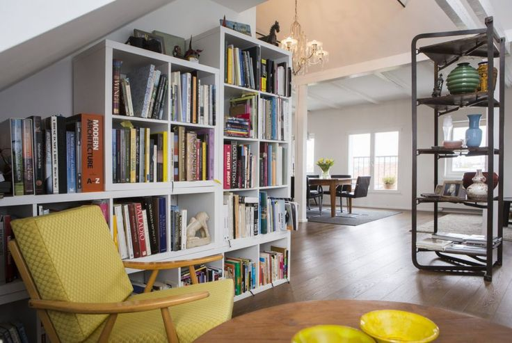White library combined with an yellow armchair. Combination of a neutral and bright color creates a timeless contrast  Yellow tableware gives a finishing touch. Grey and white modern dining room furnished with a big wooden table, Ludwig Mies van der Rohe Brno chairs,grey carpet and a collection of pictures on the wall. #yellow  #grey  #library  #armchair  #modern  #contrast  #interior  #design  #homedecor