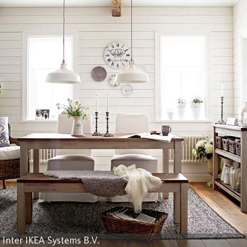 Die weiße Holzverkleidung der Wand erzeugt eine friedliche, cleane Atmosphäre in dem Esszimmer. Der Korbsessel und die Aufbewahrungsboxen in Braun setzen …