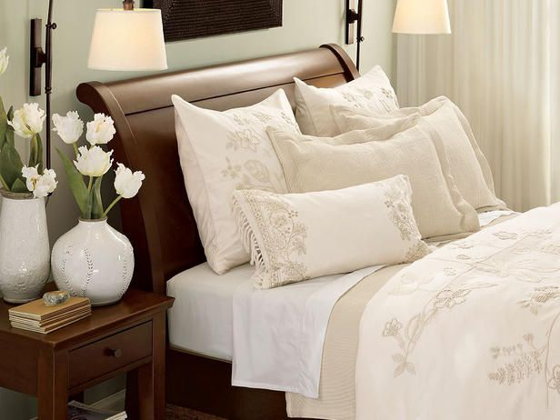 Flowing Floral White-and-ivory floral bed linens freshen a traditional bedroom and perfectly contrast against the dark wood sleigh bed. Go shopping