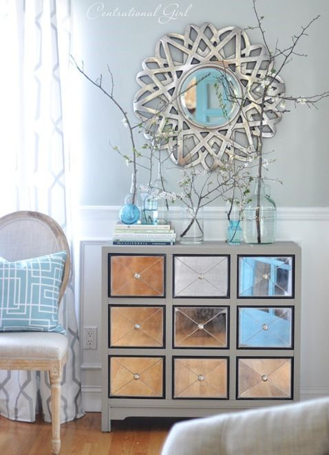 living room mirror and chest. paint a piece of furniture with drawers. Attach mettal sheet or reflective sheet to it and ad around the edges trim or tacks for furniture to give it a metalic, reflective look.