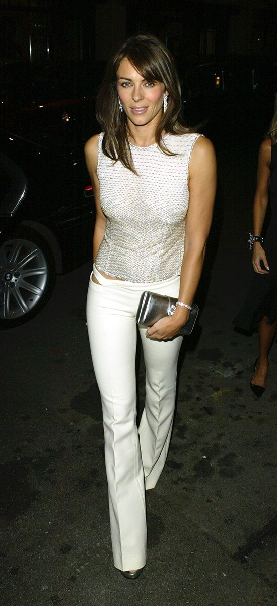 Elizabeth Hurley in Versace top and white pants, accessorized with metallic clutch.