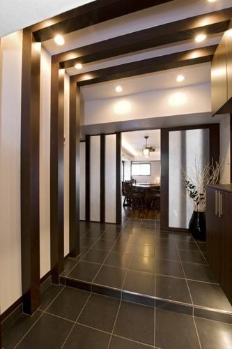 古民家風の化粧梁と化粧柱、ガラス壁を組み合わせ、光の演出効果をプラスした上質感あふれるエントランス。既存の収納スペースを取り払い、ゆったりとした広がりを確保。