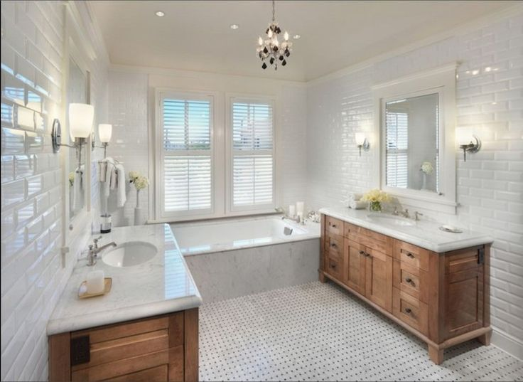 Gorgeous bathroom with matching oak vanities facing each other paired with undermount sinks and marble counters over marble tiled floors with black dot accent. The vanities are finished with white inset mirrored medicine cabinets flanked by polished nickel wall sconces over beveled subway tiled walls. A drop-tub with marble surround and tub deck stands at the far end of the bathroom below plantation shuttered windows and a mini black crystal chandelier.