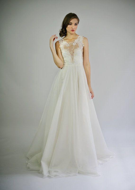 Cette robe de mariée unique présente un beau corsage de soie ivoire et chaire et une jupe volumineuse et sublime d'organza et soie.    Le corsage est