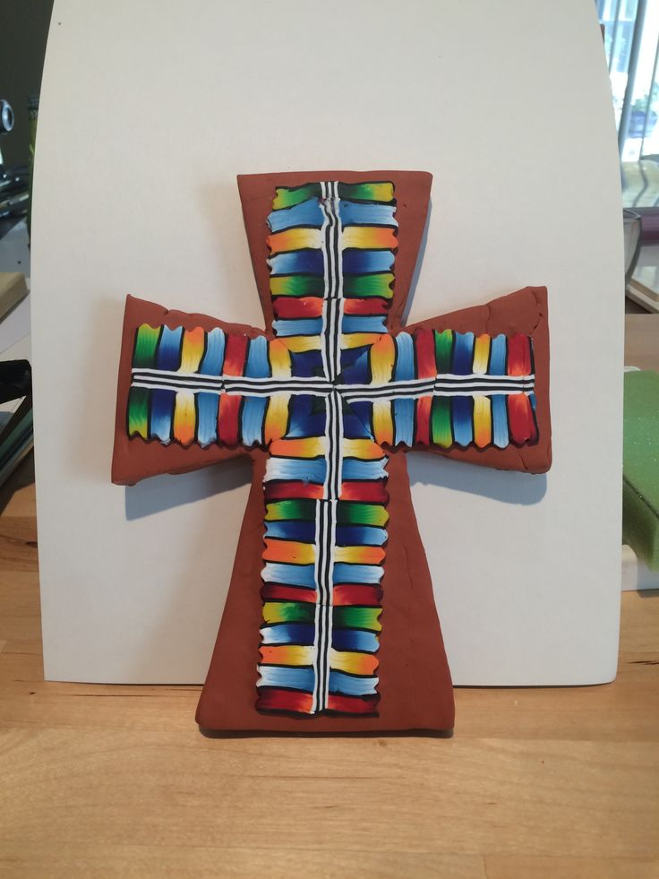 Premo rainbow colored cane slices on Sculpey III terracotta polymer clay cross. Cross baked first, then rainbow slices applied with Sculpey bake and bond, then bake again.  By Pat Brown. See this design on printable art at https://fineartamerica.com/featured/clay-cross-02-pat-brown.html.