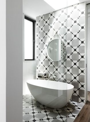 A continuous wall-to-floor monochromatic tile surface makes a bold statement in the ensuite.