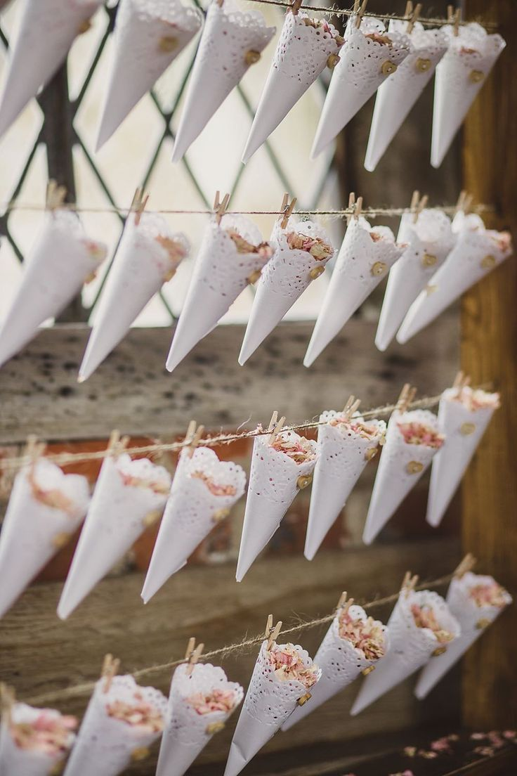 Lace doily confetti cones pegged to a wooden frame - Image by Lola Rose Photography - Pronovias Lary wedding dress for a vintage inspired wedding in a country house with garden games, 1930s gramophone music & pink colour scheme: